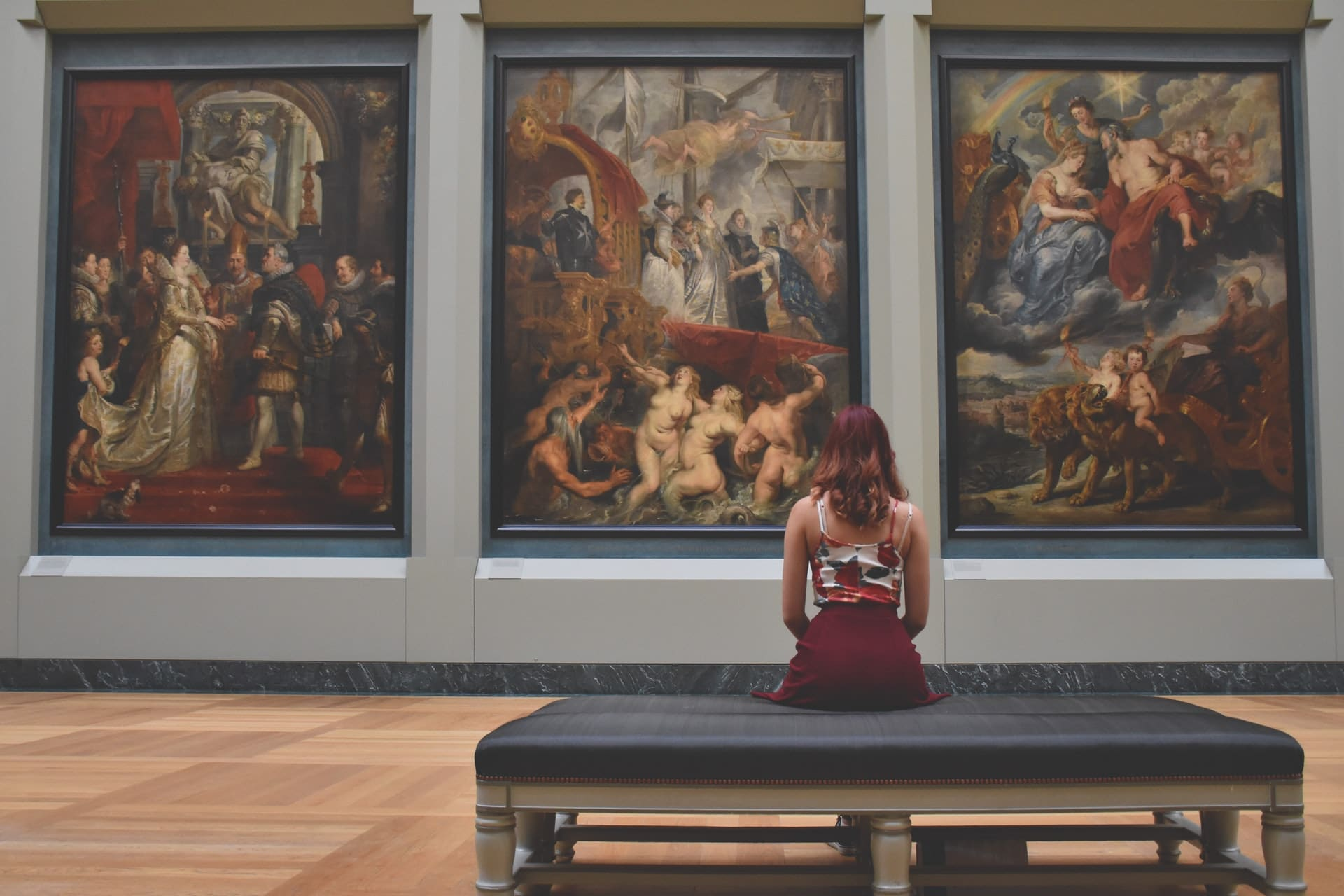 Woman sitting in museum with antique art paintings